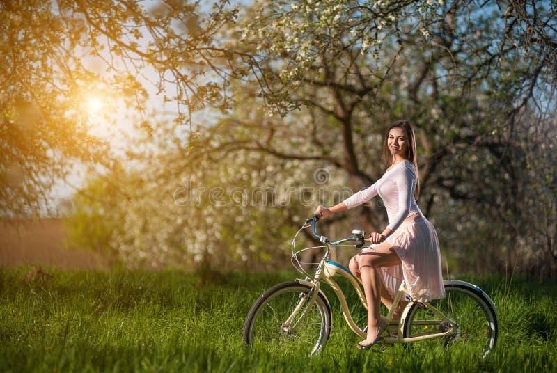 Ciclista fêmea bonito com o jardim retro da bicicleta na primavera fotografia de stock