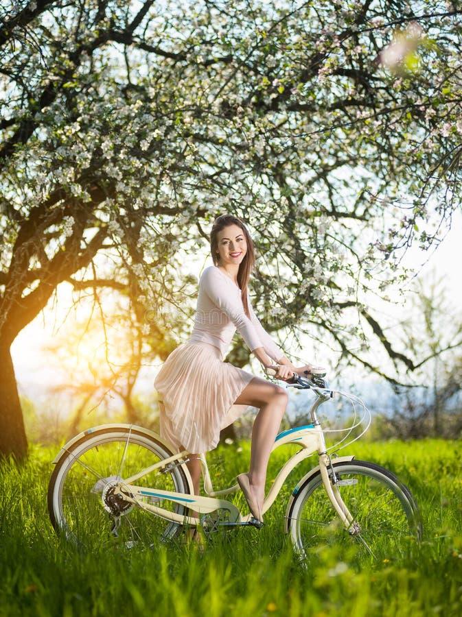 Ciclista fêmea bonito com o jardim retro da bicicleta na primavera foto de stock