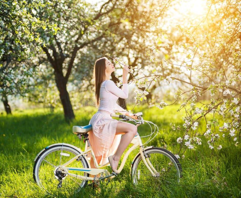 Ciclista fêmea bonito com o jardim retro da bicicleta na primavera fotos de stock royalty free
