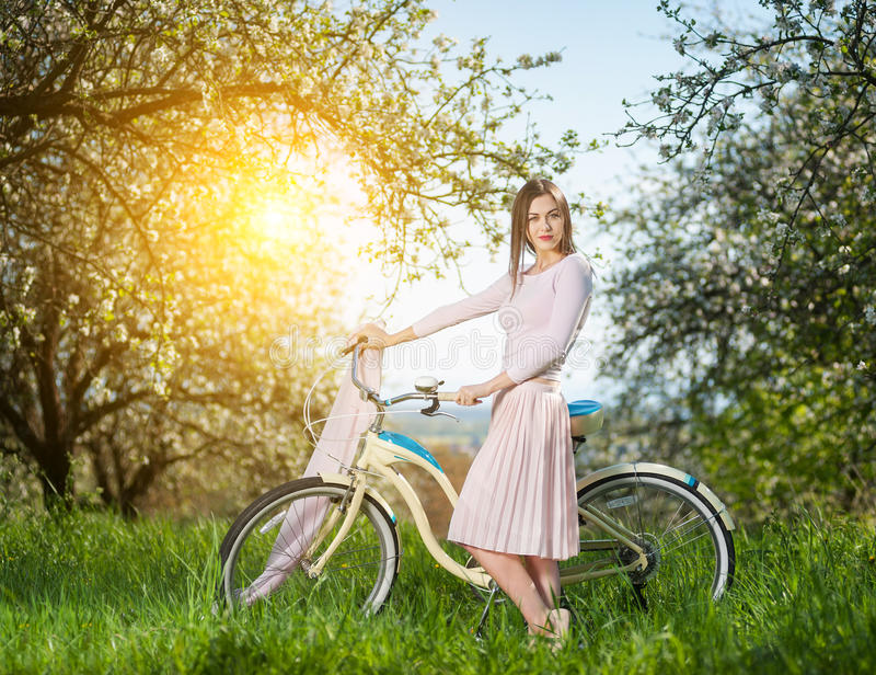 Ciclista fêmea bonito com o jardim retro da bicicleta na primavera imagem de stock