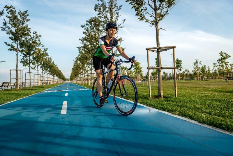 Ciclista fêmea em uma estrada do parque que tem o treinamento imagens de stock