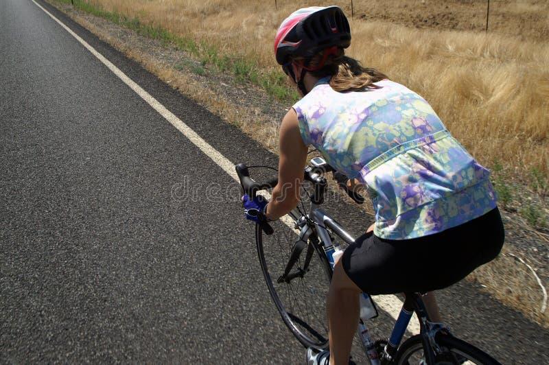 Ciclista fêmea na estrada secundária imagem de stock royalty free