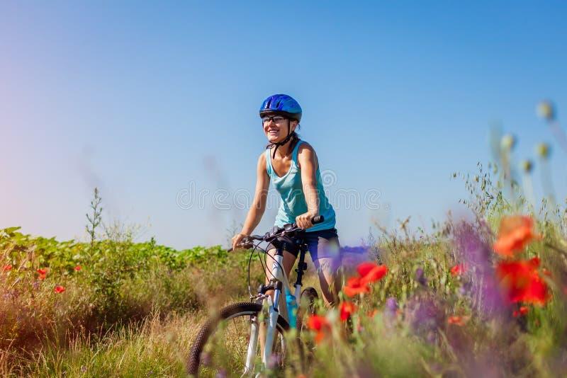 Ciclista feliz da jovem mulher que monta uma bicicleta da montanha no campo do verão Menina que tem os pés de levantamento do div imagens de stock