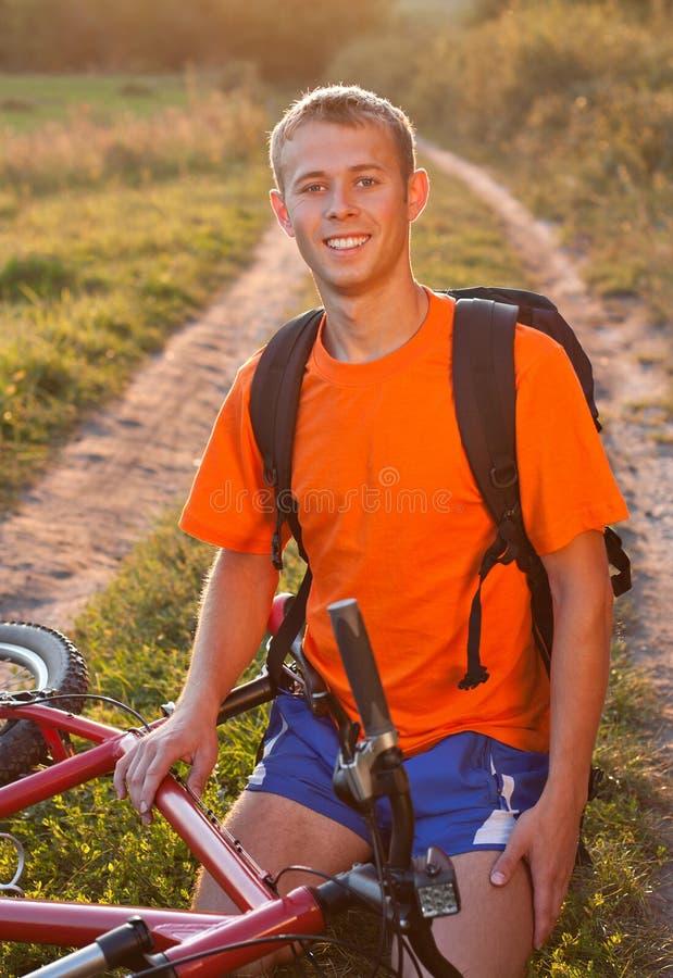 Ciclista feliz del hombre que se sienta en el camino fotografía de archivo libre de regalías
