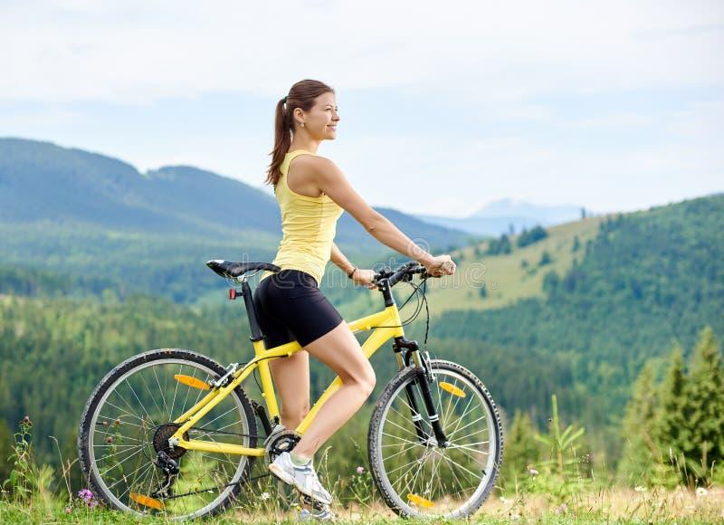 Ciclista femenino atractivo con la bicicleta amarilla de la monta?a, disfrutando de d?a soleado en las monta?as foto de archivo libre de regalías