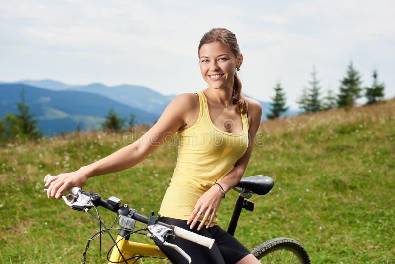 Ciclista femenino atractivo con la bicicleta amarilla de la monta?a, disfrutando de d?a soleado en las monta?as imagen de archivo