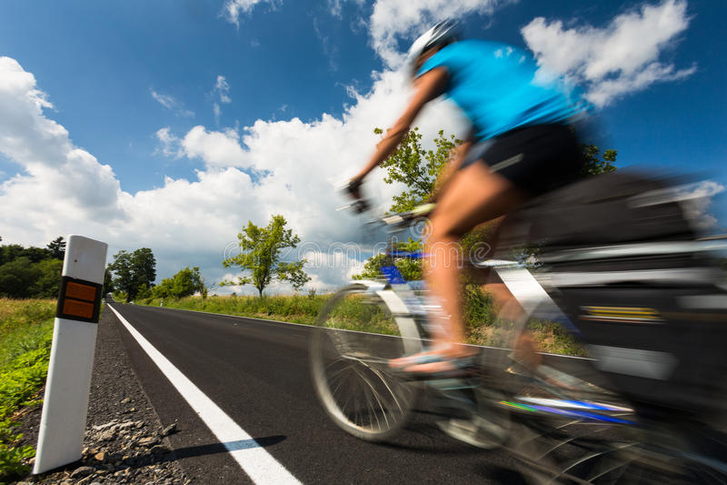 Ciclista femenino biking en una carretera nacional foto de archivo