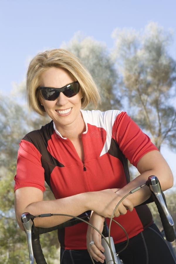 Ciclista femenino que se inclina en la bicicleta foto de archivo libre de regalías