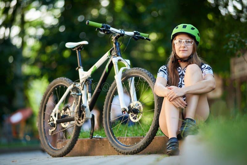 Ciclista femenino que se sienta cerca de la bici foto de archivo libre de regalías