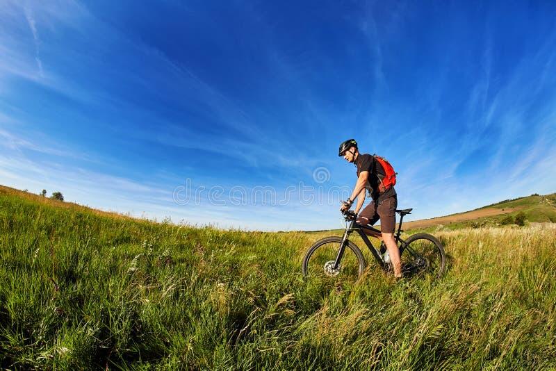 Ciclista joven de la montaña del montar a caballo del ciclista contra puesta del sol hermosa en el campo fotografía de archivo