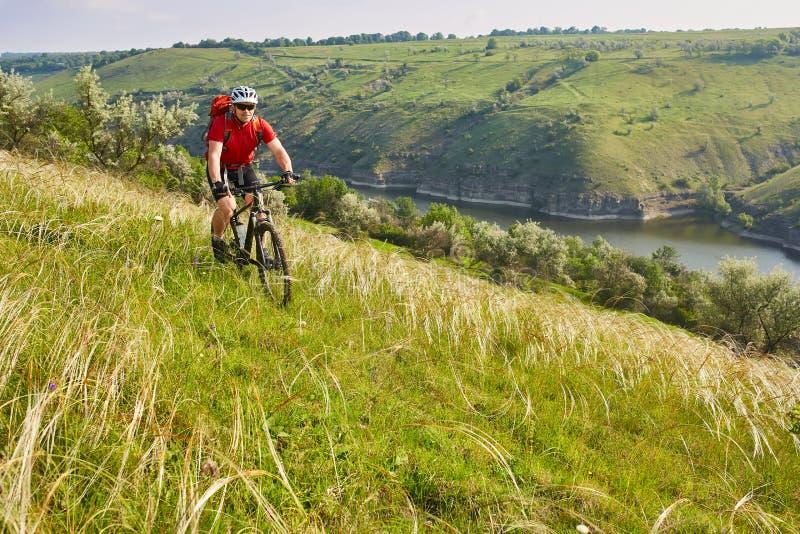 Ciclista joven que completa un ciclo en el prado verde del verano contra paisaje hermoso fotografía de archivo libre de regalías