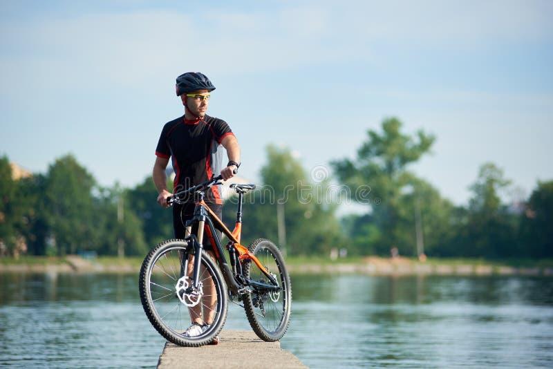 Ciclista maschio che prende rottura accanto alla bici vicino al lago della città immagine stock libera da diritti