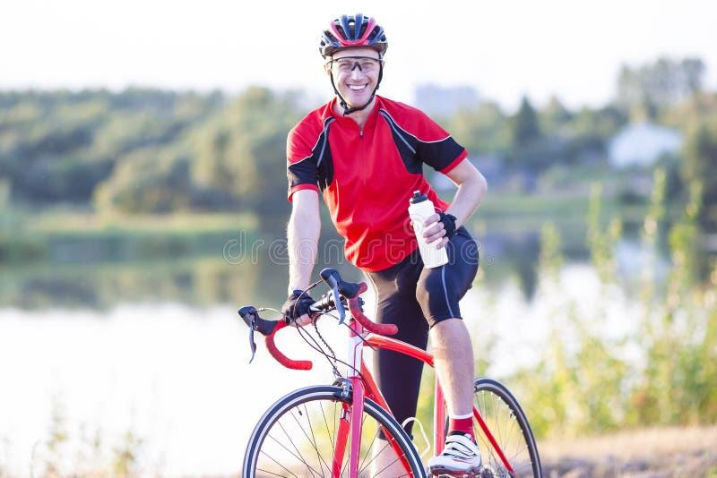 Ciclista maschio sorridente felice che ha un resto e che posa con la bottiglia fotografie stock