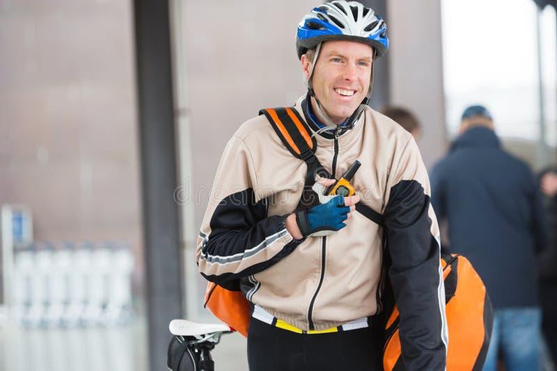 Ciclista masculino con el mensajero Bag Using Walkie-Talkie fotos de archivo