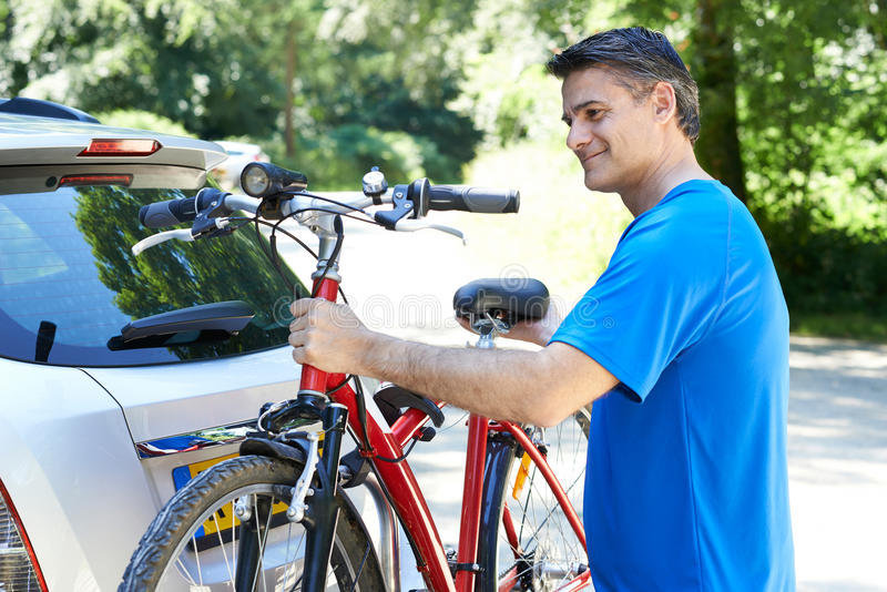 Ciclista masculino maduro que toma la bici de montaña del estante en el coche imagen de archivo