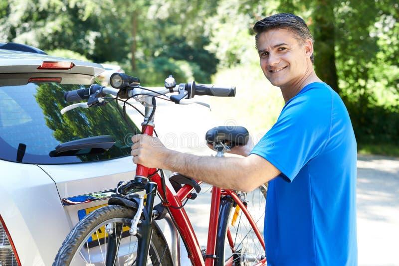 Ciclista masculino maduro que toma la bici de montaña del estante en el coche foto de archivo