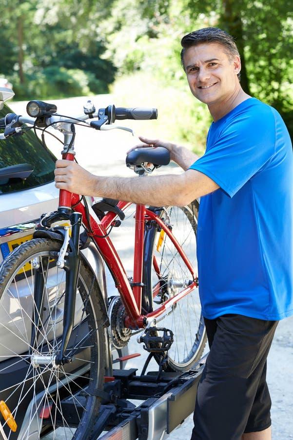 Ciclista masculino maduro que toma la bici de montaña del estante en el coche fotografía de archivo