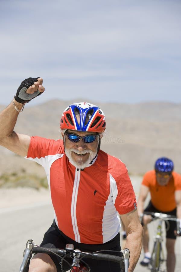 Ciclista masculino mayor que celebra su victoria imágenes de archivo libres de regalías