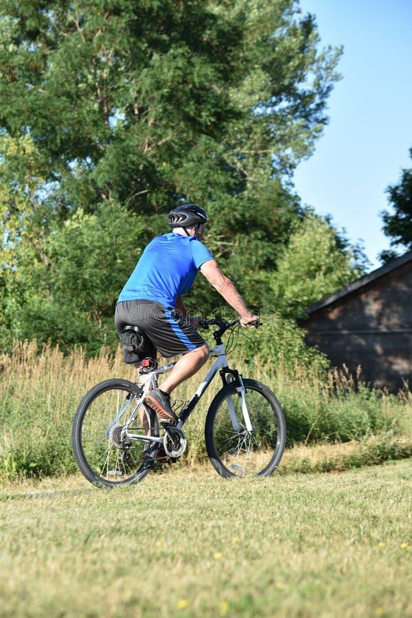 Ciclista masculino que ejercita la bici que monta foto de archivo