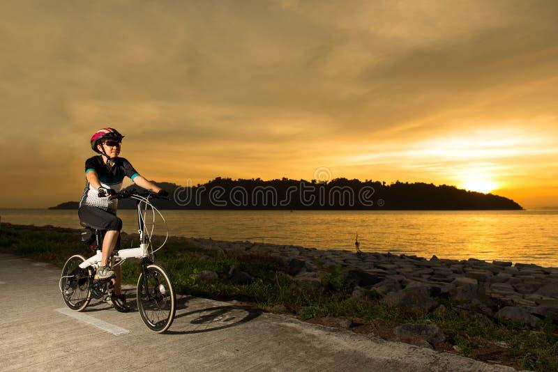 Ciclista mayor de la mujer en la puesta del sol foto de archivo