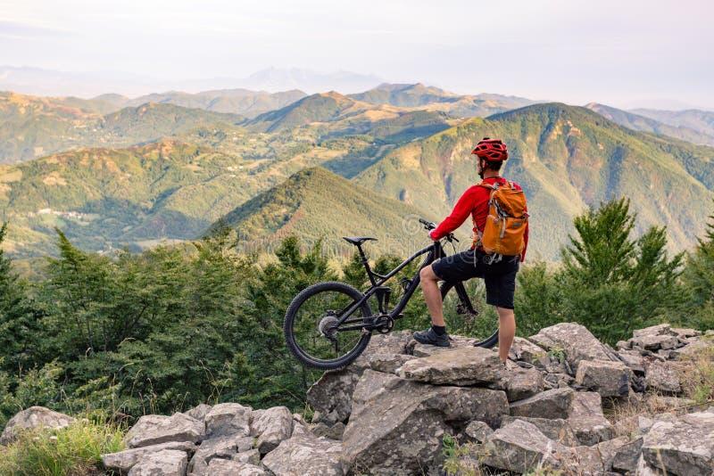 Ciclista in mountain-bike che esamina vista sulla traccia della bici in montagne di autunno fotografia stock