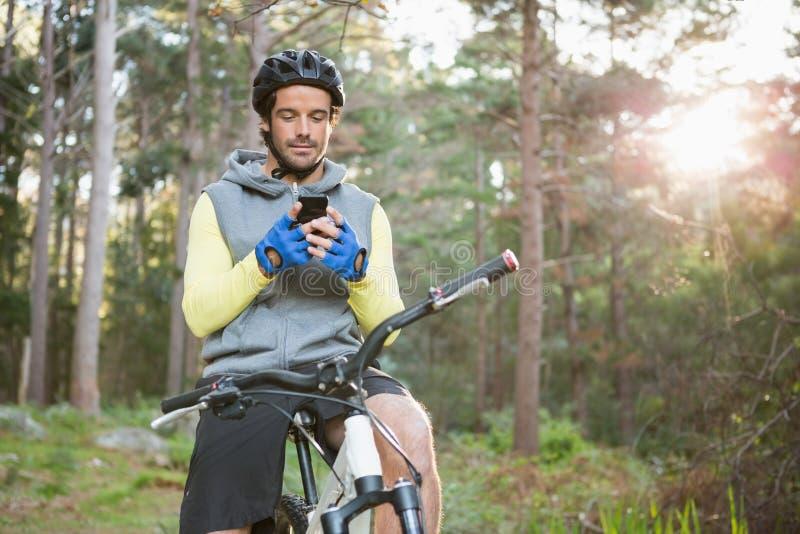 Ciclista in mountain-bike che per mezzo del telefono cellulare immagine stock