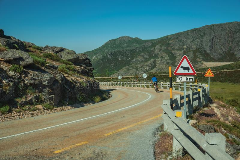 Ciclista na estrada que passa com a paisagem rochosa fotografia de stock