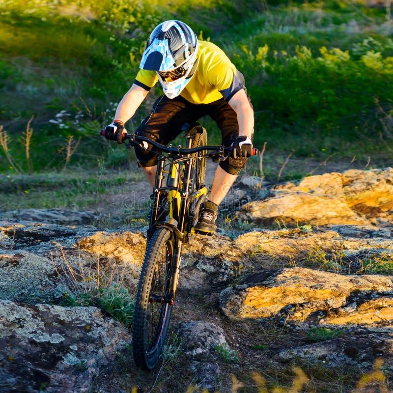 Ciclista no Mountain bike amarelo para baixo Rocky Hill do t-shirt e da equitação do capacete Conceito extremo do esporte imagem de stock