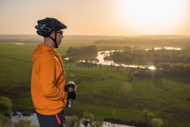 Ciclista no por do sol nas montanhas Um homem novo em um capacete e em vidros bebe a água de uma garrafa imagem de stock