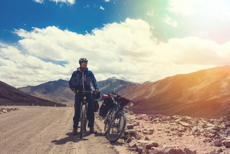 Ciclista novo que está na estrada da montanha, estado de Jammu e Caxemira, Índia norte fotografia de stock royalty free