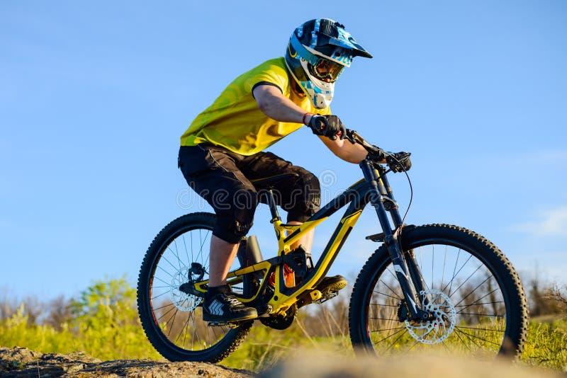 Ciclista profesional en la bici de montaña amarilla de la camiseta y del montar a caballo del casco abajo Rocky Hill Concepto ext fotos de archivo libres de regalías
