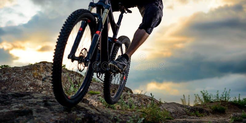 Ciclista profesional que monta la bici abajo Rocky Hill en la puesta del sol Deporte extremo Espacio para el texto imágenes de archivo libres de regalías