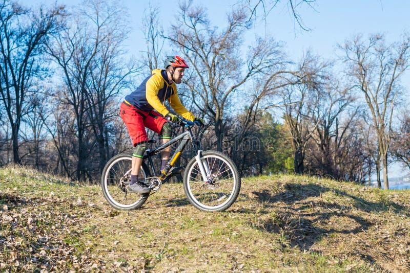 Ciclista professionista in un maglione giallo e in uno shertakh rosso che guidano giù una collina, spazio libero Stile di vita at immagini stock