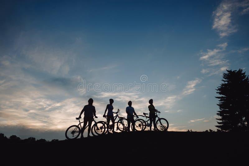 Ciclista quattro sulla collina ad uguagliare cielo fotografia stock libera da diritti