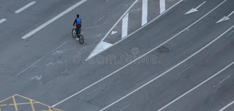 Ciclista que cruza pistas vazias em nenhum dia dos carros em Barcelona imagem de stock