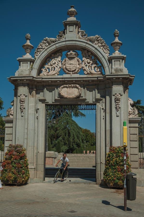 Ciclista que cruza a porta de Felipe IV no parque do EL Retiro no Madri foto de stock royalty free