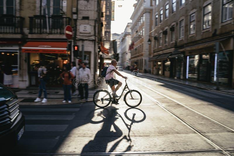 Ciclista que cruza uma interseção na cidade foto de stock