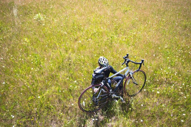 Ciclista que descansa da viagem ao sentar-se no prado com as flores da grama e do campo que guardam sua bicicleta fotografia de stock