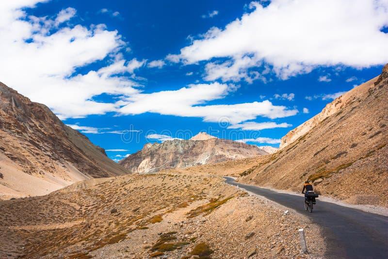 Ciclista que está na estrada das montanhas himalayas imagem de stock royalty free