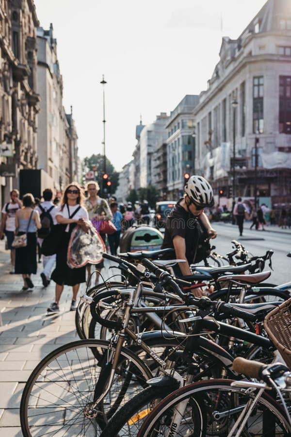 Ciclista que estaciona sua bicicleta em Oxford Street, Londres, Reino Unido foto de stock
