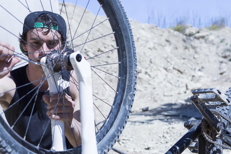 Ciclista que fija la rueda de la bici de BMX fotos de archivo libres de regalías