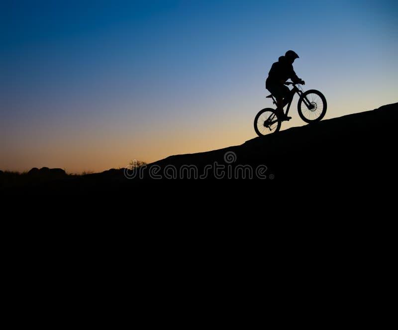 Ciclista que monta a bicicleta em Rocky Trail no por do sol Esporte extremo e conceito Biking de Enduro foto de stock royalty free