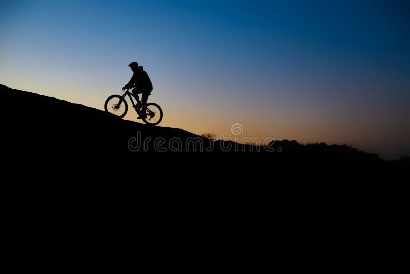 Ciclista que monta a bicicleta em Rocky Trail no por do sol Esporte extremo e conceito Biking de Enduro imagens de stock