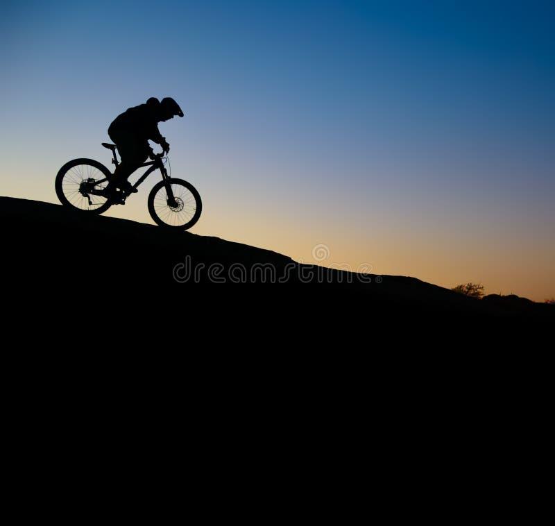 Ciclista que monta a bicicleta em Rocky Trail no por do sol Esporte extremo e conceito Biking de Enduro fotografia de stock royalty free