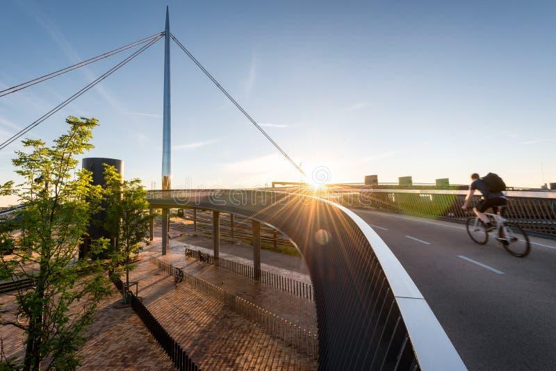 Ciclista que pasa el puente de la ciudad y el x28; Bro& x29 de Byens; en Odense, Denmar imagen de archivo