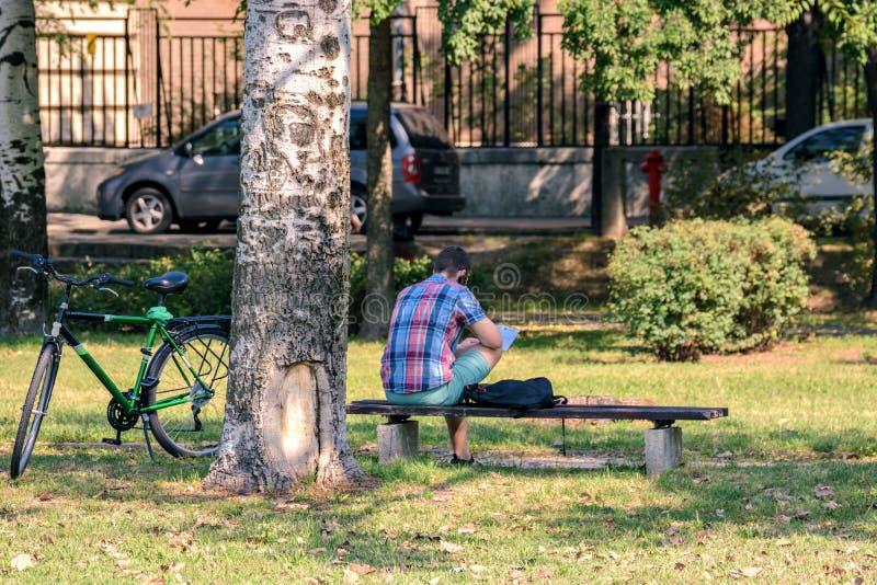 Ciclista que senta-se em um banco fotografia de stock
