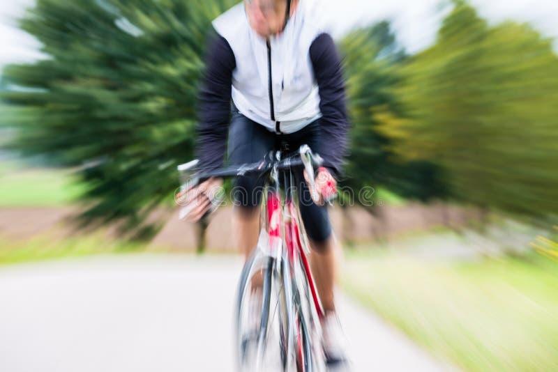 Ciclista rápido do esporte na bicicleta com borrão de movimento fotografia de stock