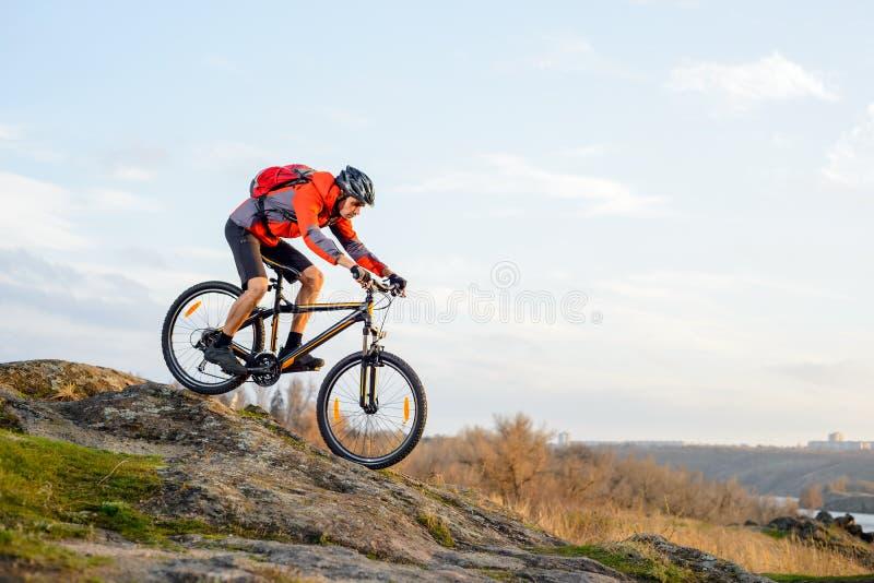 Ciclista in rivestimento rosso che guida la bici giù Rocky Hill Sport estremo fotografia stock libera da diritti