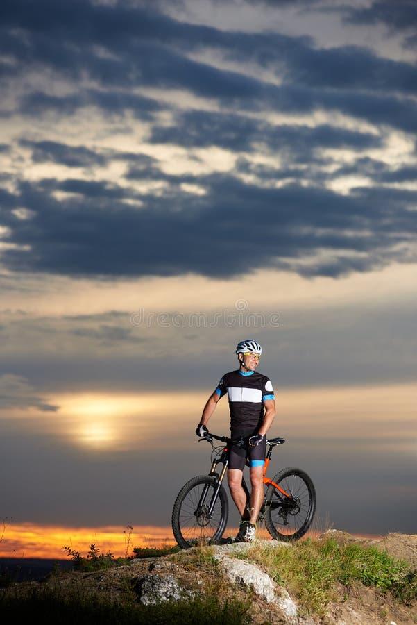 Ciclista robusto y sonriente que presenta cerca de la bici imagen de archivo libre de regalías