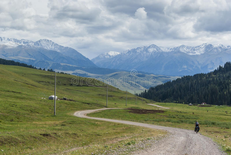 Ciclista só nas montanhas de Quirguizistão fotografia de stock